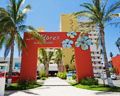 Entrance of Las Flores Beach Resort with parking lot.