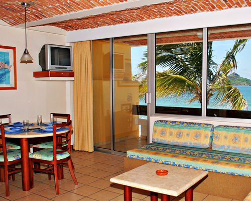 A well furnished living room with a television dining area and balcony with ocean view.
