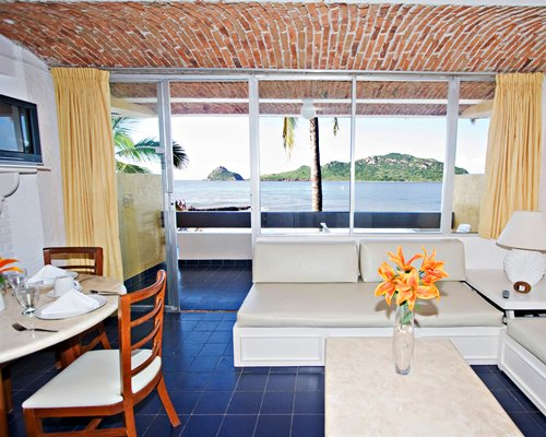 A well furnished living room with a television dining area patio and view of ocean.