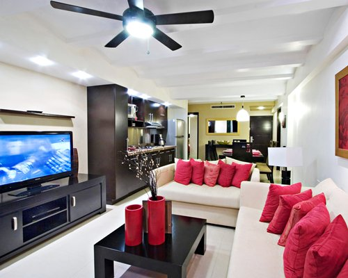 A well furnished living room with open plan kitchen television and dining area.