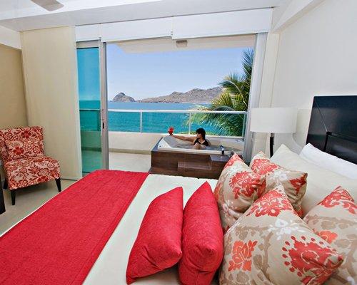 A well furnished bedroom with a balcony bathtub and ocean view.