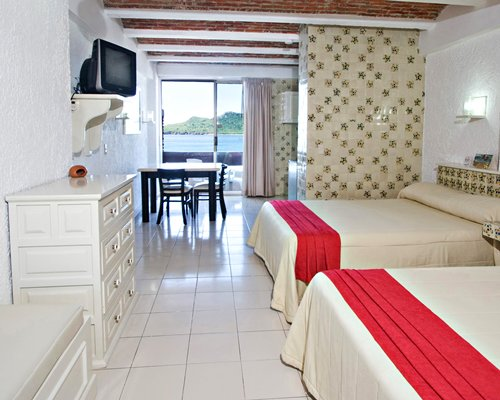 A well furnished bedroom with two beds television dining area patio and ocean view.
