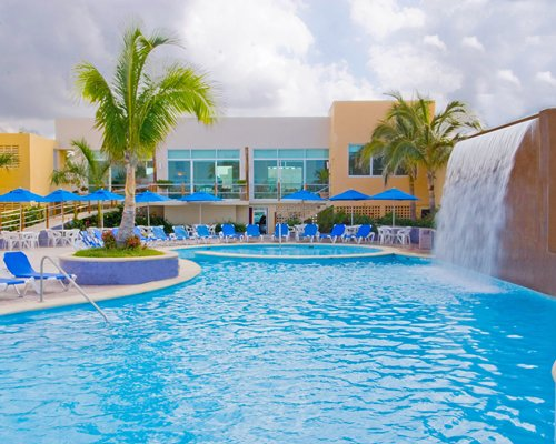Outdoor swimming pool with waterfalls chaise lounge chairs sunshades and palm trees.