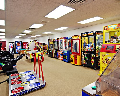 An indoor recreation room with pool table and arcade games.