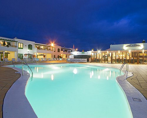 An outdoor swimming pool alongside the resort units at night.