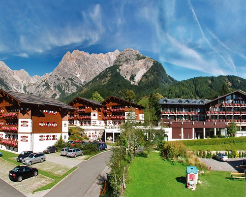Exterior view of Marco Polo Club Alpina alongside the mountains.