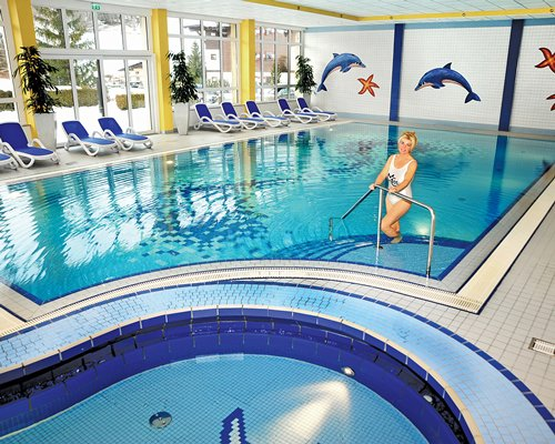 A women standing in the indoor swimming pool and hot tub with chaise lounge chairs.