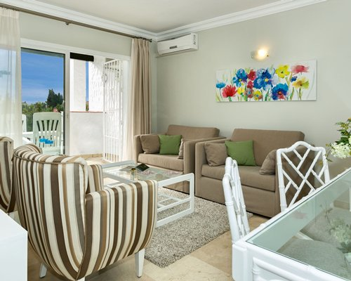 A well furnished living room with dining area and balcony.