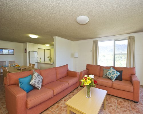 A well furnished living room with dining area open plan kitchen and outside view.