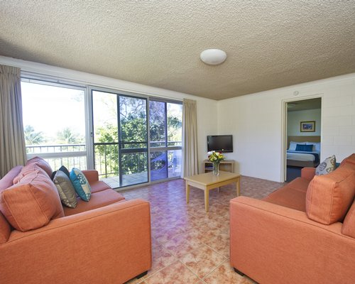 A well furnished living room with balcony and view of a bedroom.