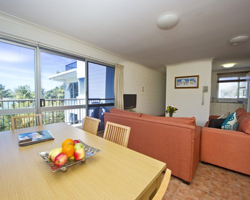 A well furnished living room with open plan kitchen dining area television and balcony.