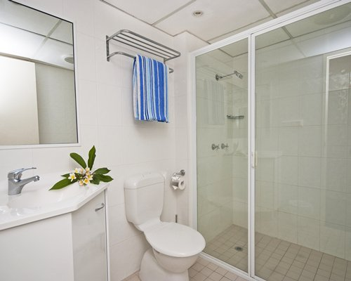 A bathroom with stand up shower toilet and single sink vanity.