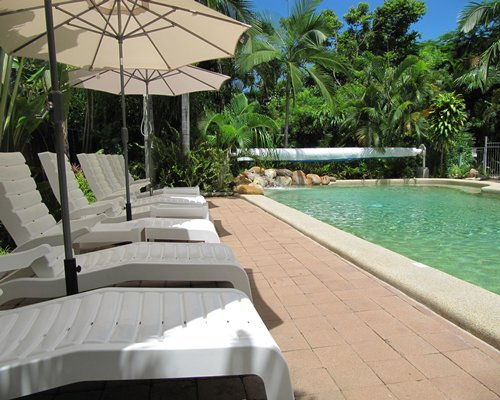 Outdoor swimming pool with chaise lounge chairs and sunshades.
