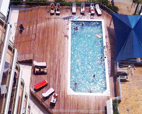 An aerial view of an outdoor swimming pool with chaise lounge chairs and sunshade alongside multiple balconies.
