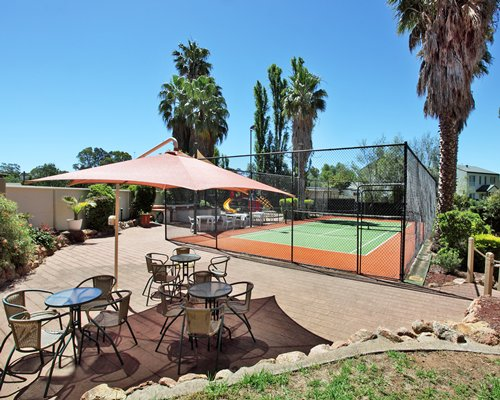 Outdoor dining with sunshades and pathway to tennis court.