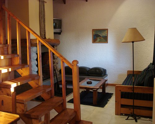 A well furnished living room with fireplace and stairway.