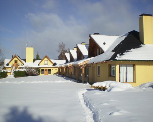 Exterior view of Las Lomas del Correntoso resort covered by snow.