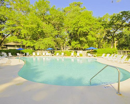 An outdoor swimming pool with chaise lounge chairs and sunshades surrounded by wooded area.
