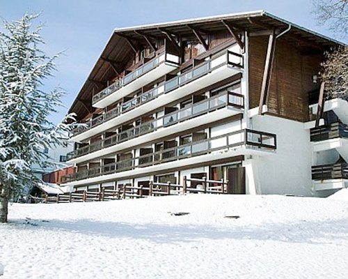 A street view of the Maeva Clubhotel Megeve Mont D'Arbois covered in snow.