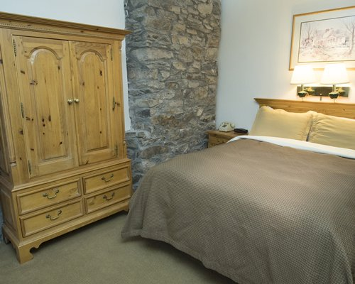 A well furnished bedroom with queen bed and wardrobe.