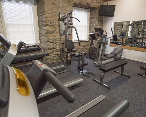 A well equipped indoor fitness center with television.