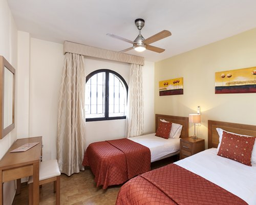 A well furnished bedroom with two beds and mirror.