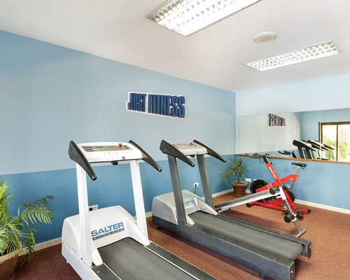 A well equipped fitness center and outside view.