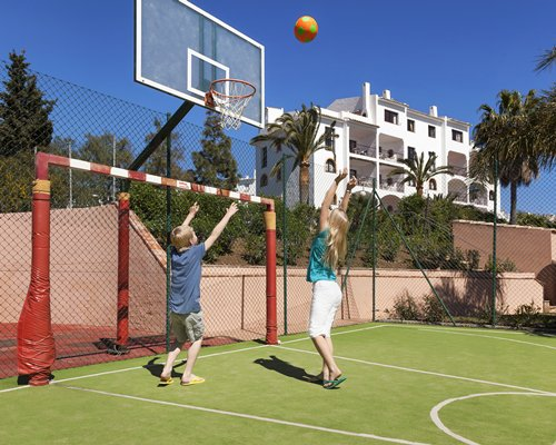 View of two kids playing in an outdoor basketball court.