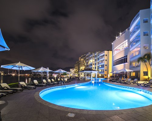 An outdoor swimming pool with chaise lounge chairs and poolside bar alongside the beach.