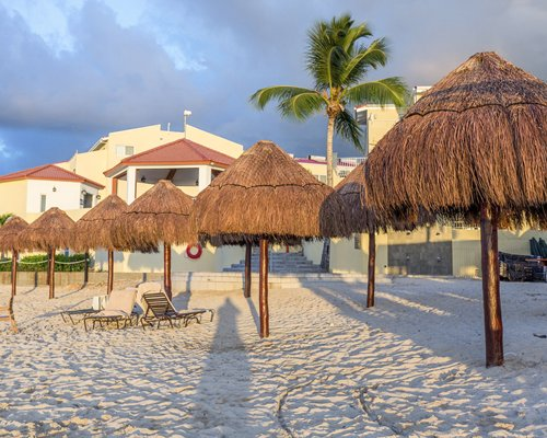 Beach view of thatched sunshades and chaise lounge chairs alongside the resort.