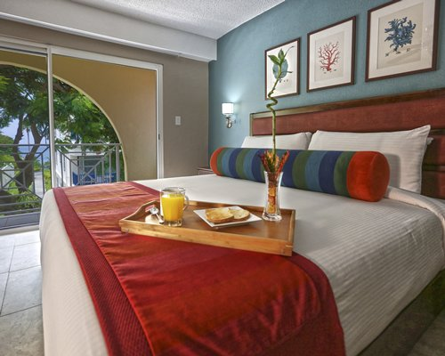 A well furnished bedroom with food on the bed and outdoor view.