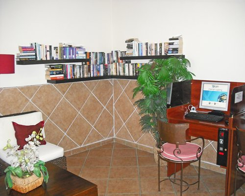 A well furnished common room with a computer and library.