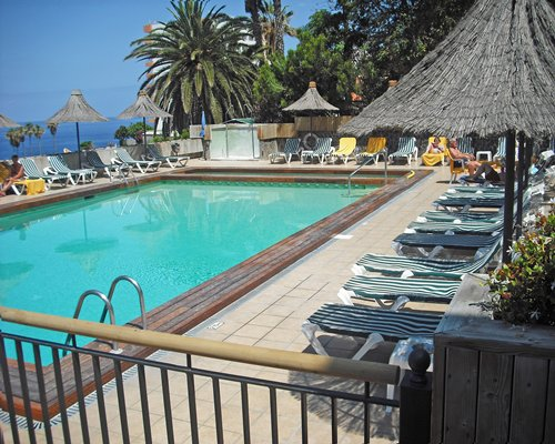 An outdoor swimming pool with thatched sunshades and chaise lounge chairs.