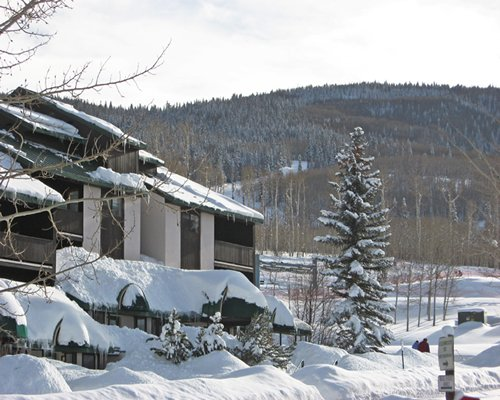 Snow covered exterior view of Goldenwoods Condominiums At Powderhorn Resort alongside mountains.