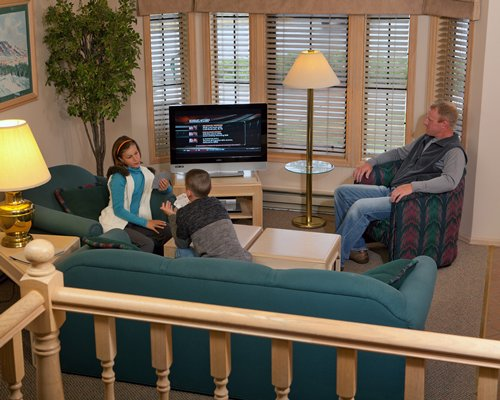 A family in the well furnished living room with television.