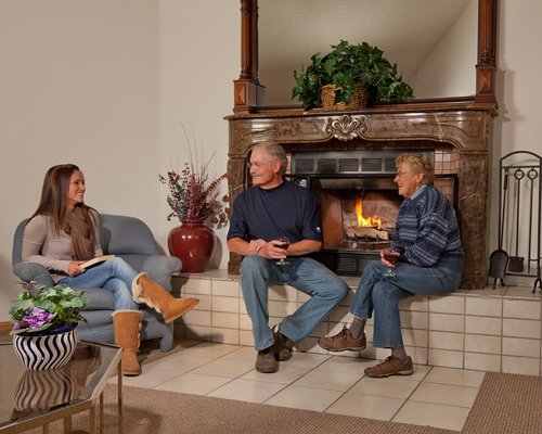 A family in the well furnished living room with the fire in the fireplace.