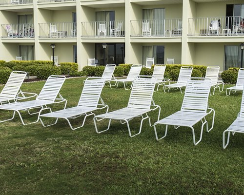 View of multiple unit balconies and chaise lounge chairs .