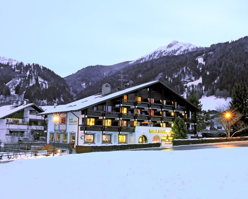 An exterior view of Ferienclub Schloesslhof resort covered in snow.