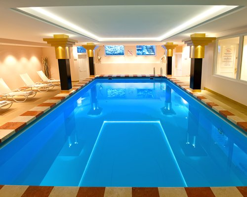An indoor swimming pool with the chaise lounge chairs.