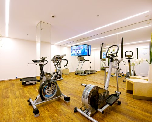 A well equipped indoor fitness area with a television.