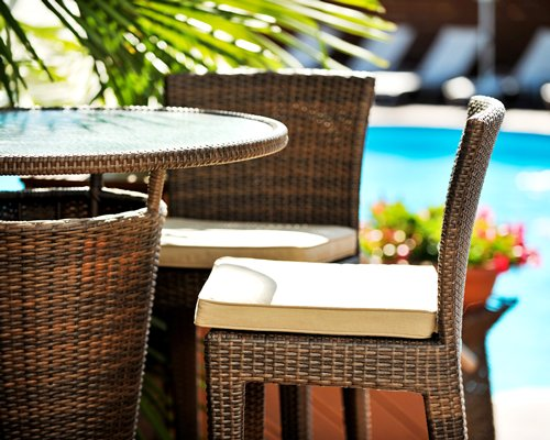 A view of the patio furniture alongside the outdoor swimming pool.