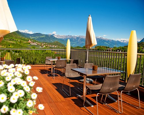 Balcony with outdoor dining and sunshades alongside wooded area and mountains.