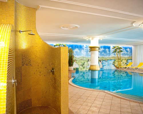 A well furnished indoor swimming pool alongside the stand up shower.