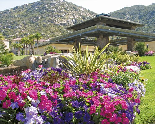 Scenic exterior view of the Resort Villas by Welk Resorts with assorted flowers alongside mountains.