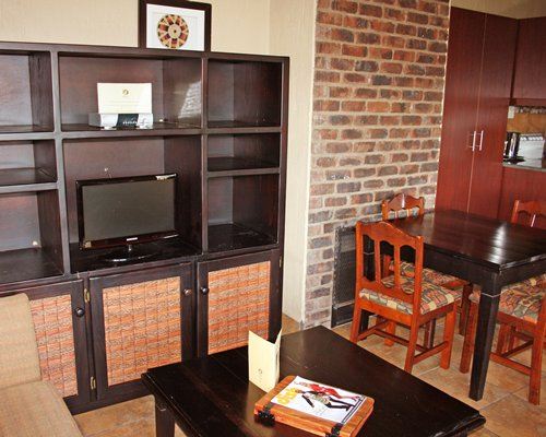 A well furnished living room with television and dining table.
