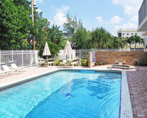 Outdoor swimming pool and hot tub with chaise lounge chairs and sunshades.