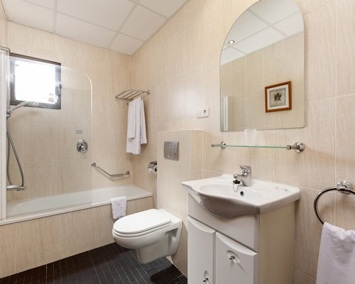A bathroom with a shower stand toilet sink and a vanity.