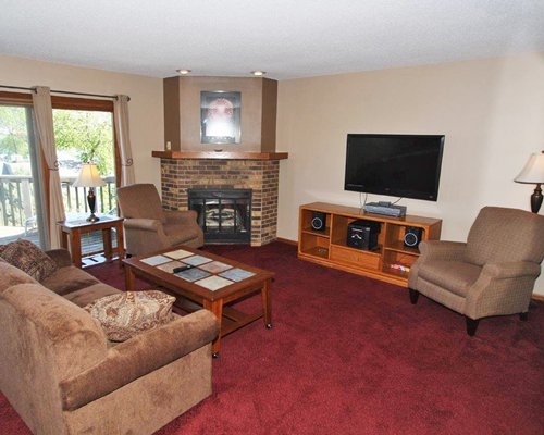 A well furnished living room with a television fireplace and a balcony.