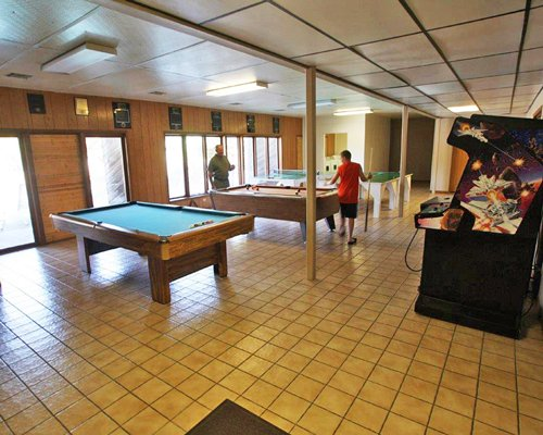 Indoor recreation room with arcade games pool table and ping pong.