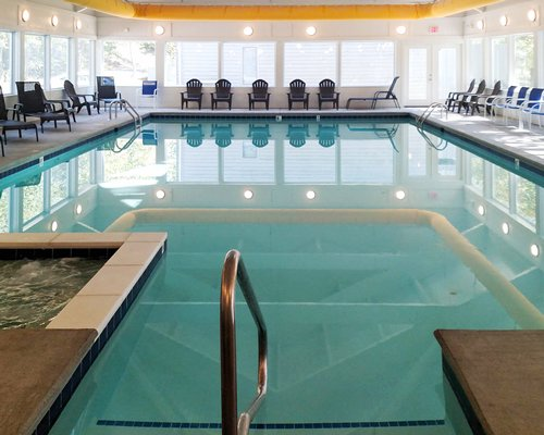 A large indoor swimming pool with patio furniture.